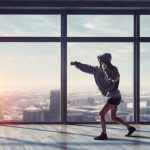 Young boxer woman exercising in empty room in lights of sunrise. Mixed media