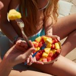 Crop of girlfriends eating fresh fruits in bowl. Focus on blonde girl in blue bikini with bowl.