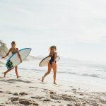 Rio De Janeiro - Two Sexy Female Surfer Girls Running Towards Ocean With Surfboard Under Arm