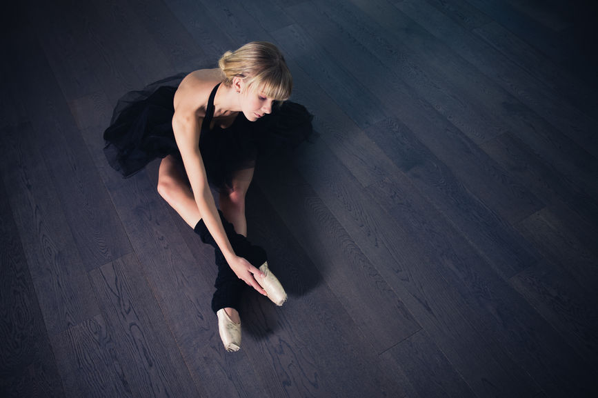 Overhead view of a blonde ballerina in a black tutu stretching on a hardwood floor.