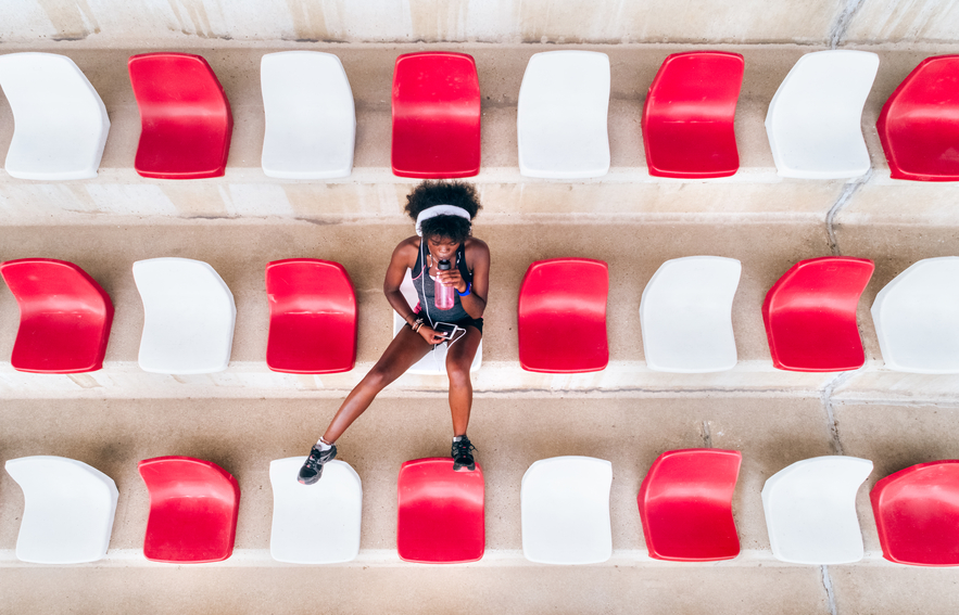 Top view of a black woman athlete in an athletics stadium listening to music with headphones